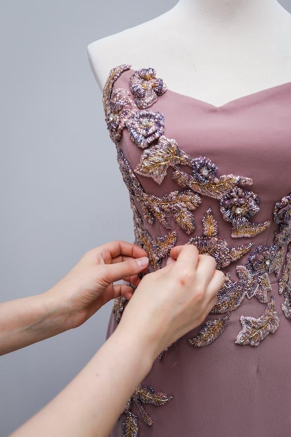 Accrocher fait main de la robe des femmes rose-clair de concepteur sur un mannequin blanc avec un ornement des perles d'or, grise photo libre de droits