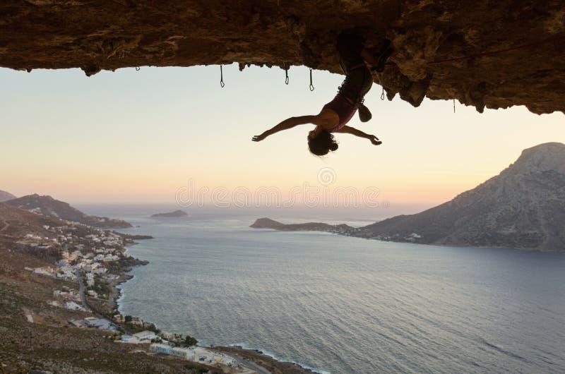 Accrocher femelle de grimpeur de roche à l'envers sur l'itinéraire exaltant en caverne au coucher du soleil photos stock