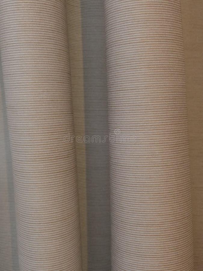 Accrocher horizontalement les rideaux beiges à nervures photographie stock libre de droits