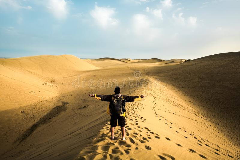 Accrocher la puissance et la sensation de la nature à un homme solitaire faisant du trekking dans les dunes du désert avec l'océa photo stock