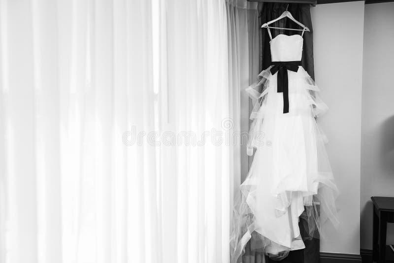 Accrocher la robe de mariage noire et blanche photos stock