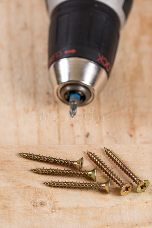 Accu drill with pile of metal screws.  royalty free stock photo