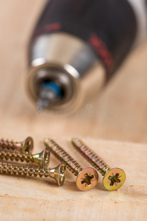 Accu drill with pile of metal screws.  stock photo