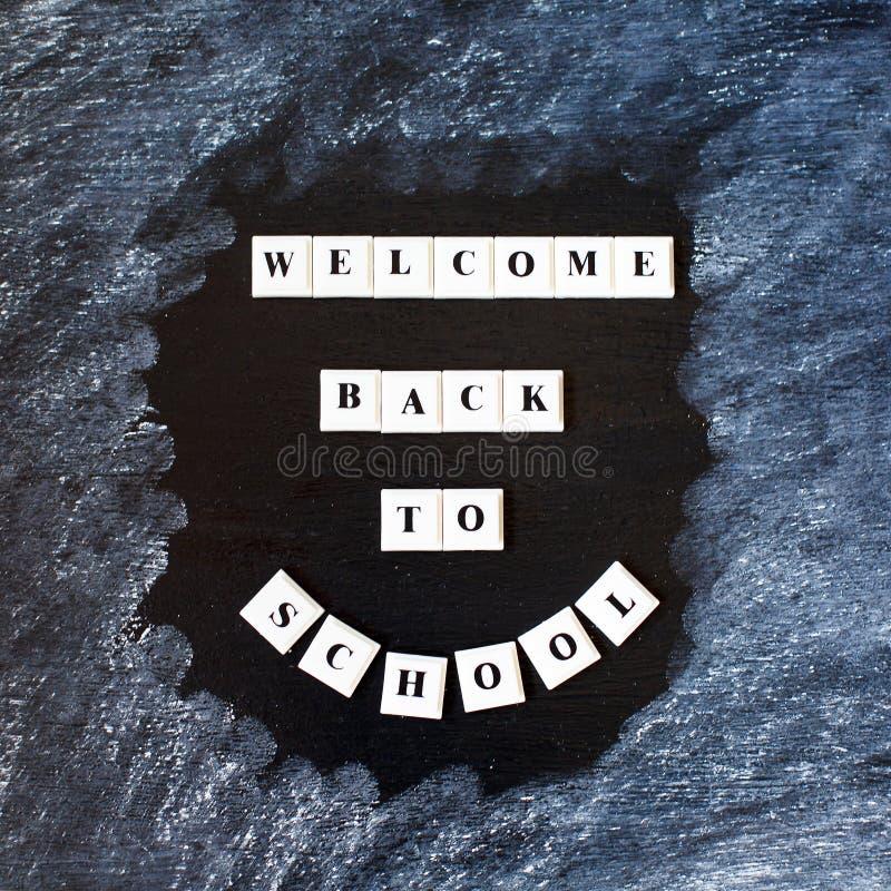 Accueil de nouveau au lettrage d'école sur le tableau noir De nouveau à l'inscription d'école sur le tableau Message sur le table photo stock