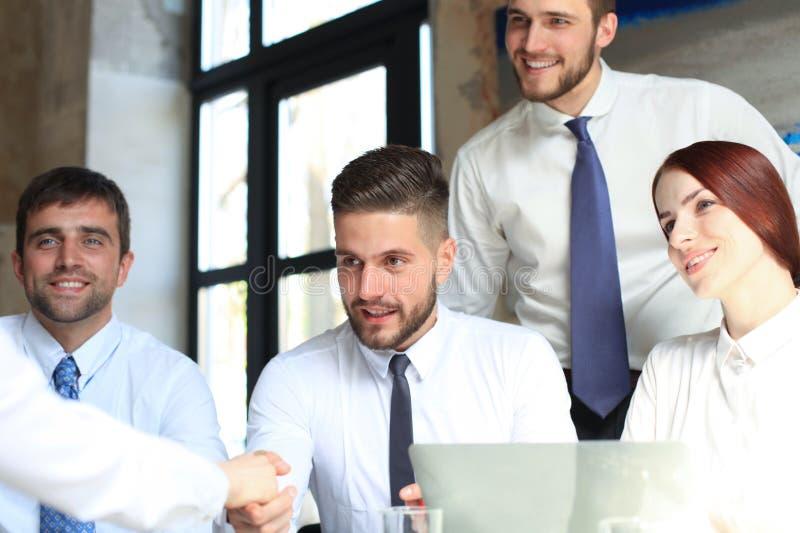 Accueil ? notre ?quipe Jeunes hommes d'affaires modernes se serrant la main tout en travaillant dans le bureau cr?atif images stock