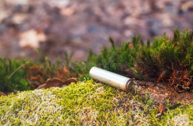 Accumulateur alcalin électrique abandonné sur la mousse dans la forêt image stock
