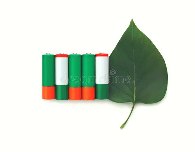 accumulateurs alcalins verts avec la feuille au-dessus d'un fond blanc photos libres de droits