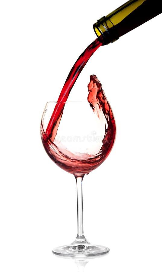 Accumulazione del vino - il vino rosso è versato in un vetro fotografia stock libera da diritti