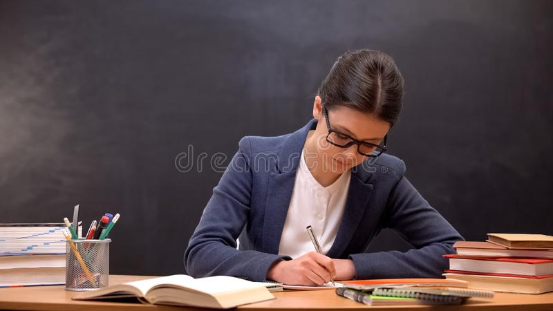 Accurate female teacher checking childrens homework sitting in school class. Stock photo stock photos