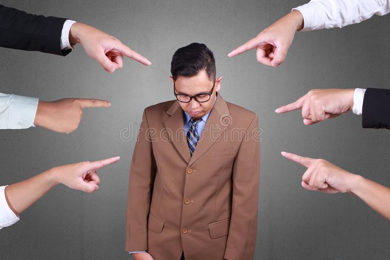 Accusation of a Guilty Businessman. Accusation guilty business person. Asian businessman get upset with many fingers pointing at him over grey background stock photo