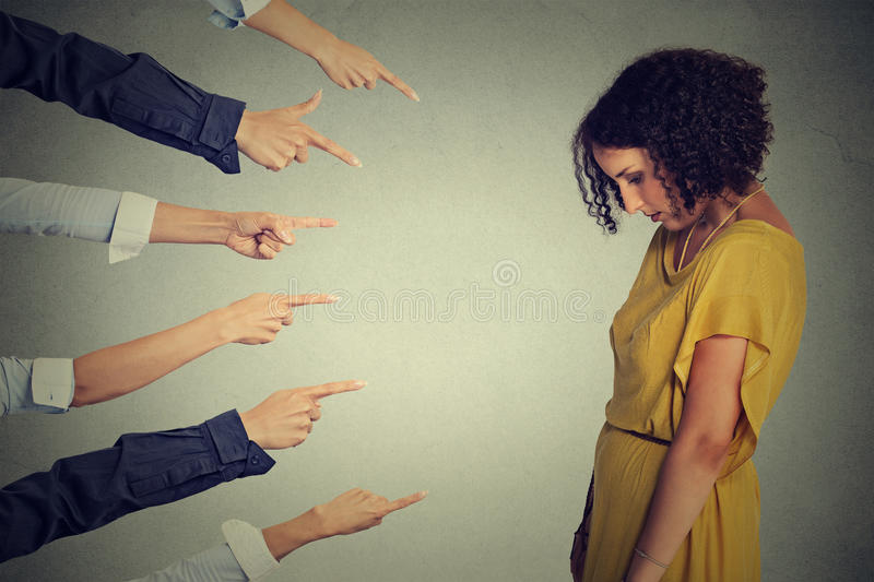 Accusation guilty person. Sad upset woman looking down many fingers pointing at her back. Concept accusation guilty person girl. Side profile sad upset woman royalty free stock image