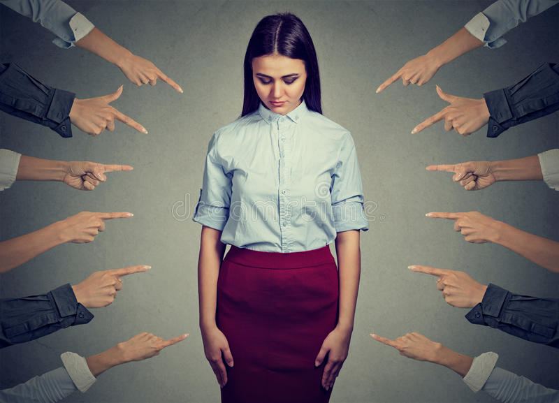 Accusation of guilty person. Sad woman looking down fingers pointing at her. Concept of accusation of guilty young person. Sad upset woman looking down many stock photography
