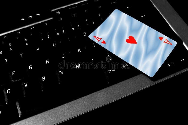 Ace av hjärtakortlögner överst av ett bärbar datortangentbord arkivfoton