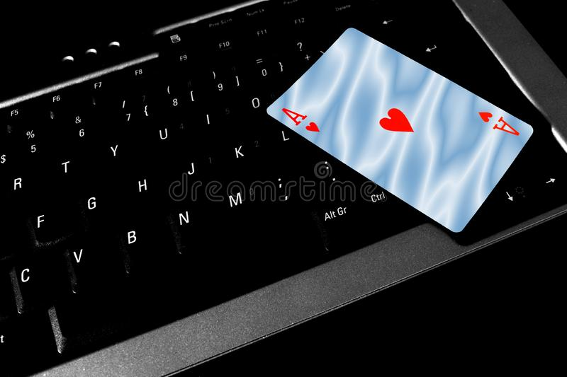 Ace of hearts card lies on top of a laptop keyboard stock photos