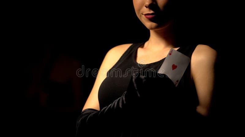 Ace que se sostiene femenino atractivo de la tarjeta de los corazones, anuncio del casino, juego de póker foto de archivo libre de regalías