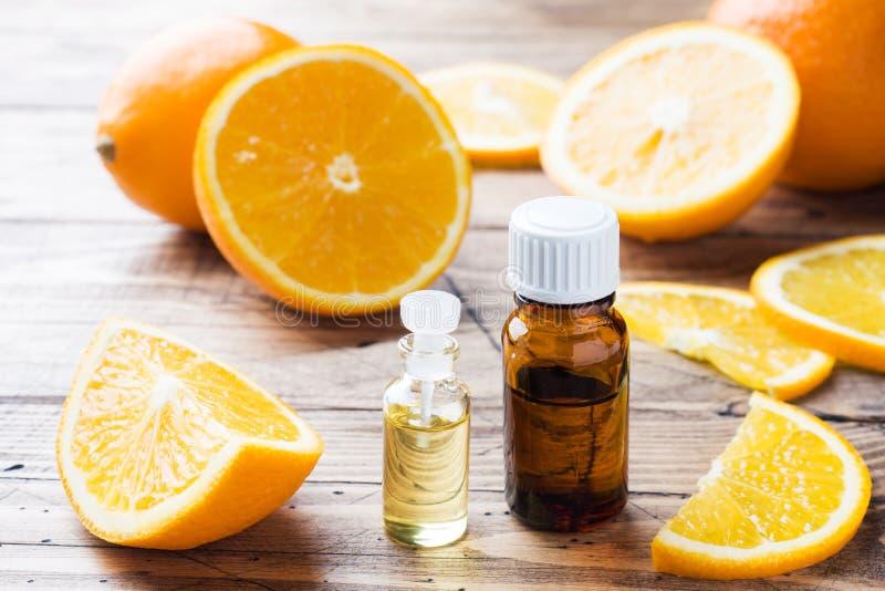 Aceite anaranjado esencial en la botella, rebanadas de la fruta fresca en fondo de madera Fragancias naturales foto de archivo libre de regalías