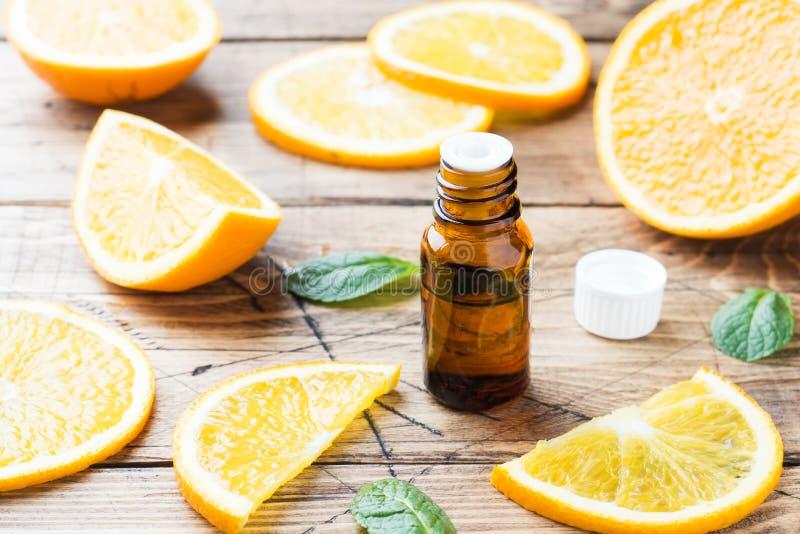 Aceite anaranjado esencial en la botella, rebanadas de la fruta fresca en fondo de madera Fragancias naturales fotografía de archivo libre de regalías