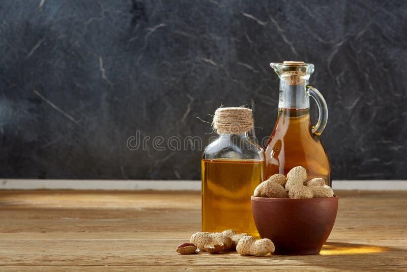 Aceite aromático en un tarro y una botella de cristal con los cacahuetes en cuenco en la tabla de madera, primer imágenes de archivo libres de regalías