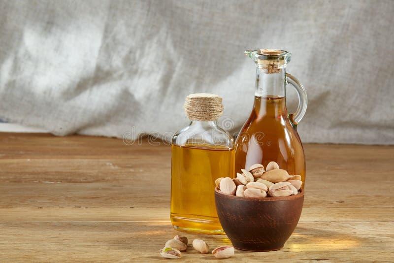 Aceite aromático en un tarro y una botella de cristal con pistacios en cuenco en la tabla de madera, primer fotografía de archivo