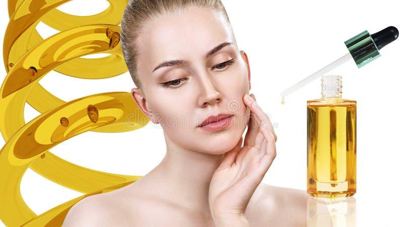 Aceite cosmético que se aplica en cara de la mujer joven fotografía de archivo
