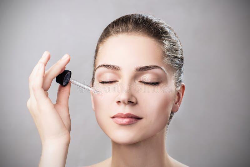 Aceite cosmético que se aplica en cara de la mujer joven imagenes de archivo