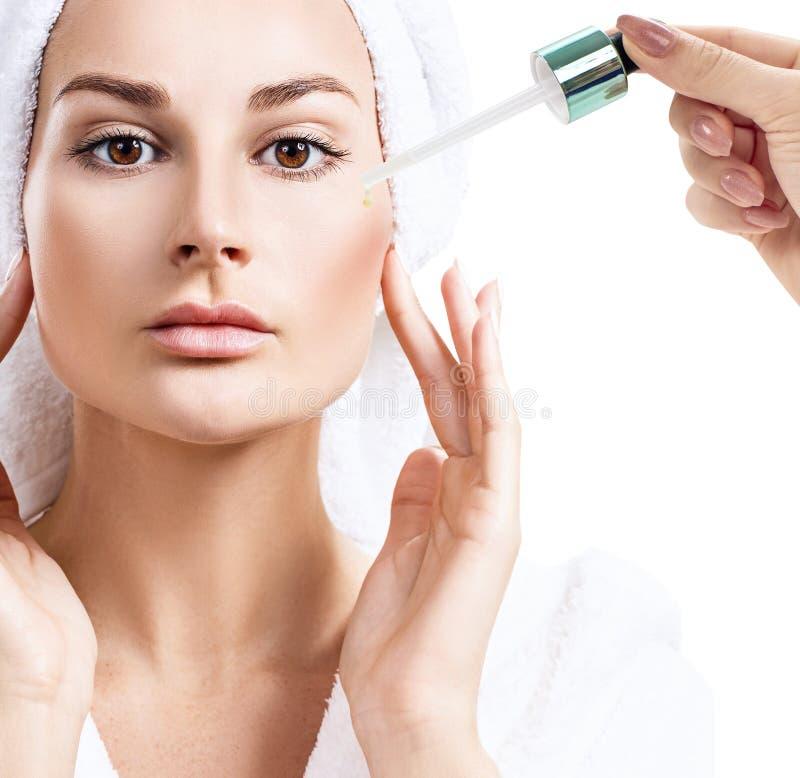 Aceite cosmético que se aplica en cara de la mujer joven fotos de archivo libres de regalías