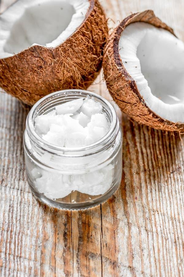 Aceite de coco para el cuidado del cuerpo en concepto cosmético en viejo tabl de madera fotografía de archivo