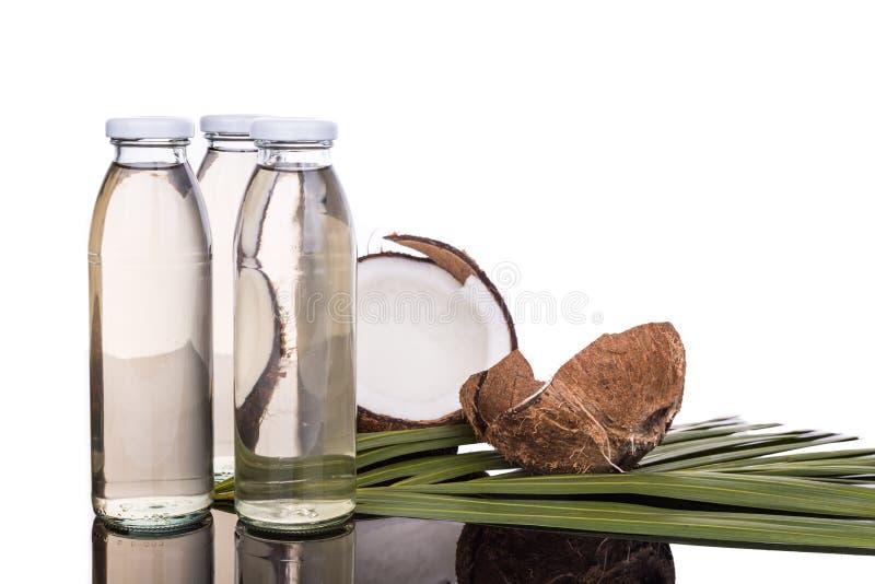 Aceite de coco virginal adicional planchado en frío en botellas con los cocos fotos de archivo libres de regalías