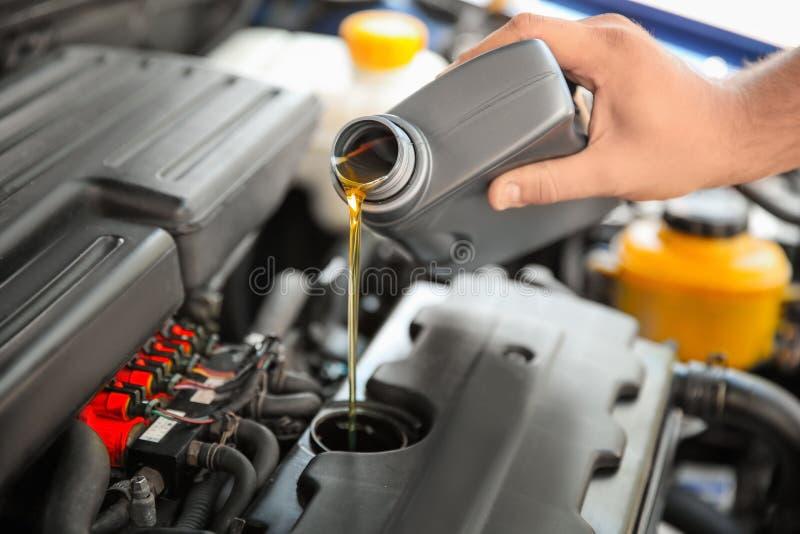 Aceite de colada del mecánico en el motor de coche fotos de archivo