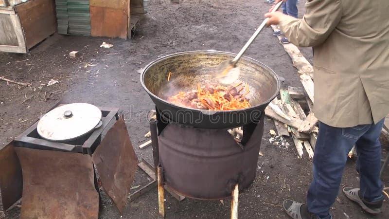 Aceite de ebullición de la agitación humana de la mano con la carne y las especias con una paleta de madera, preparación del pila almacen de video