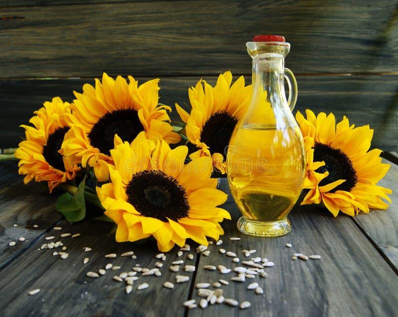 Aceite de girasol con las semillas y las flores de girasol imágenes de archivo libres de regalías
