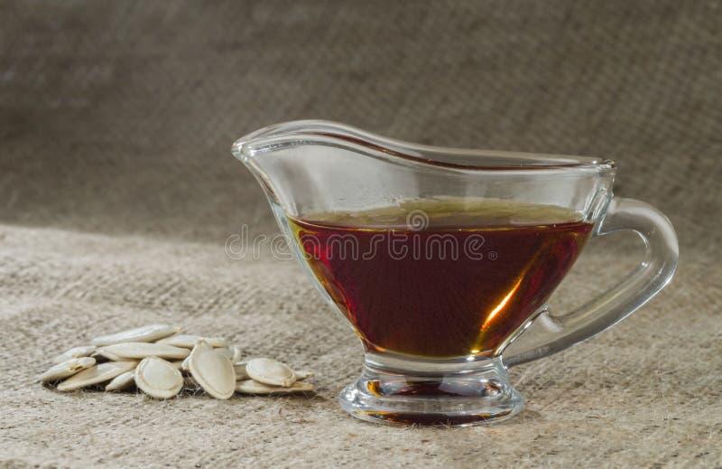 Aceite de la calabaza en una salsera de cristal y semillas de calabaza fotos de archivo libres de regalías
