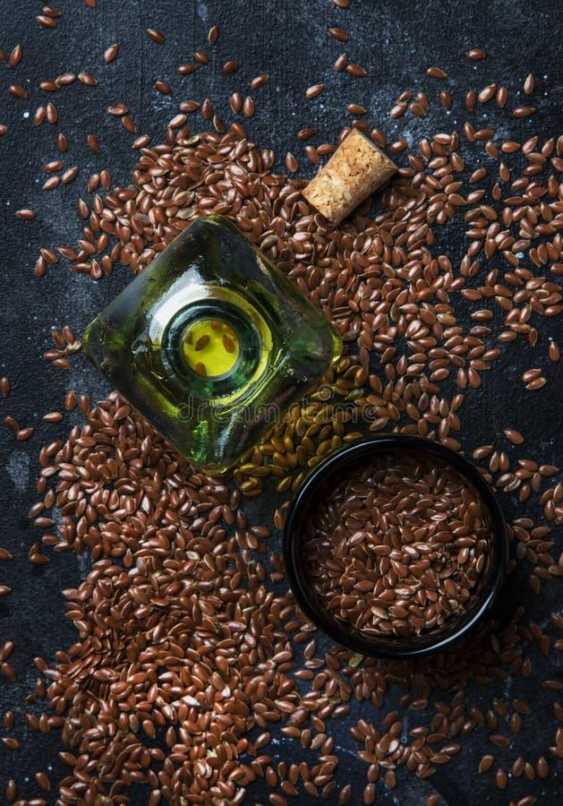 Aceite de la linaza o del lino en la botella de cristal y las semillas, fondo oscuro, imágenes de archivo libres de regalías