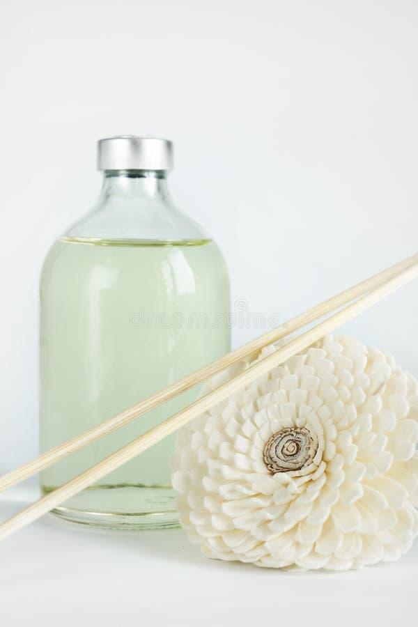 Aceite de la sandalia en una botella de cristal y los palillos para el balneario