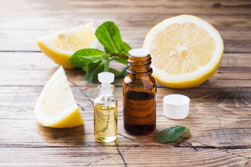 Aceite de limón esencial en la botella, rebanadas de la fruta fresca en fondo de madera Fragancias naturales imagen de archivo libre de regalías