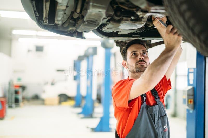 Aceite de motor cambiante del mecánico de coche de Profecional en la gasolinera de la reparación del mantenimiento fotografía de archivo