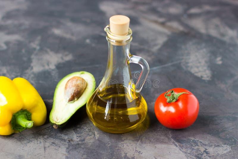 Aceite de oliva, aguacate, paprika amarilla y tomate en una foto oscura imagenes de archivo