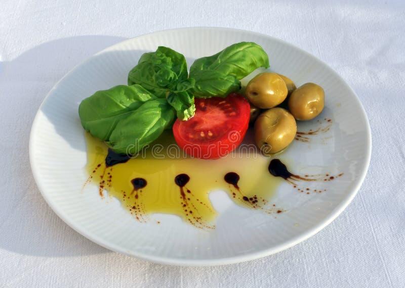 Aceite de oliva, albahaca, tomate y aceitunas verdes imagen de archivo libre de regalías