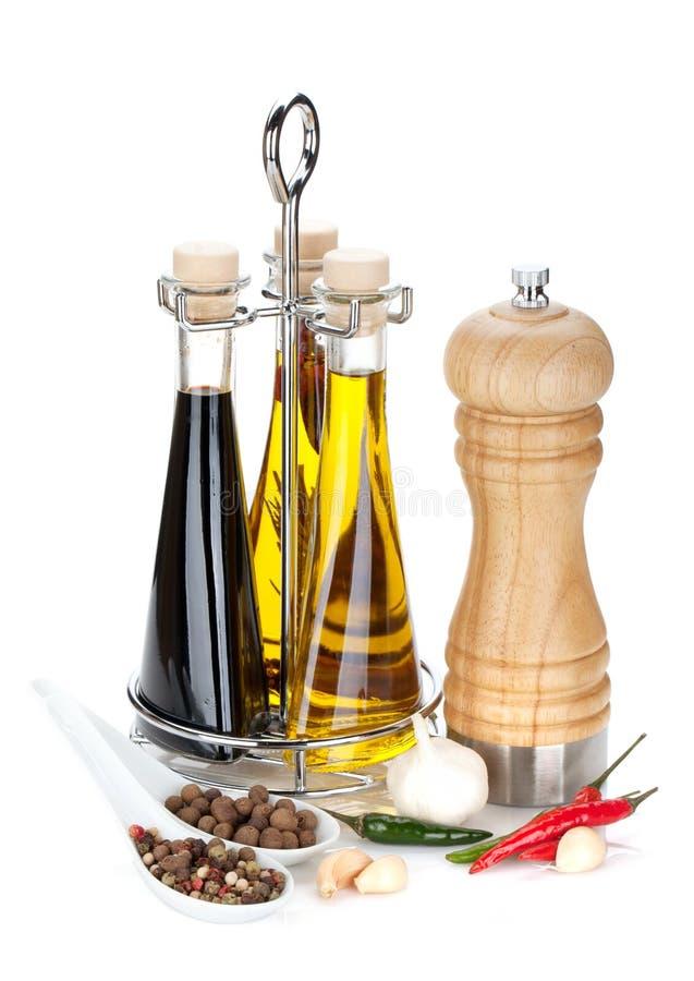 Aceite de oliva, botellas del vinagre, coctelera de la pimienta y especias foto de archivo