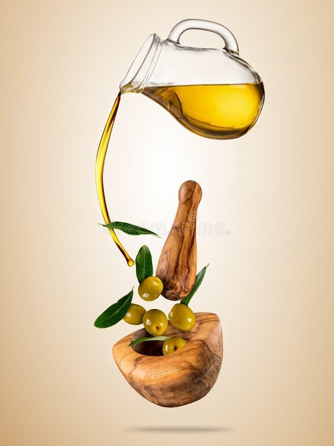 Aceite de oliva con las aceitunas del vuelo en cuenco de madera ilustración del vector