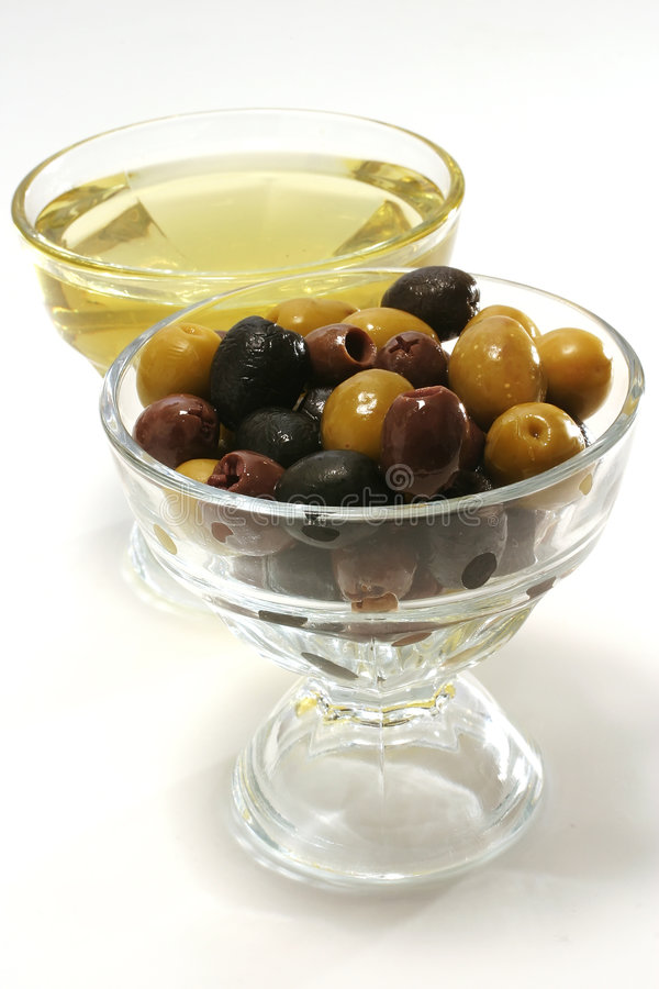 Aceite de oliva con las aceitunas verdes, negras y marrones imagen de archivo