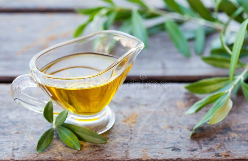 Aceite de oliva en el jarro de cristal con las ramas de olivo en fondo de madera Cierre para arriba imagen de archivo