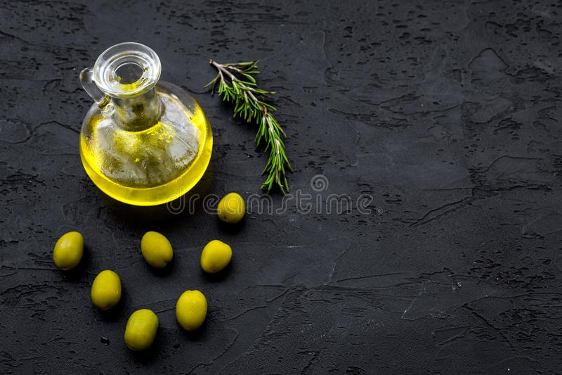 Aceite de oliva fresco en el tarro de cristal cerca de aceitunas verdes y de la rama del romero en el espacio negro de la opinión fotos de archivo