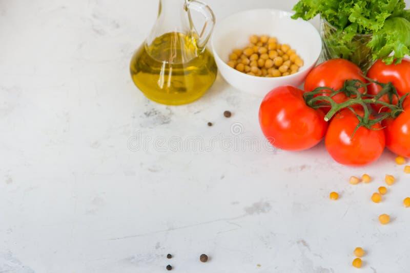 Aceite de oliva, lechuga de la ensalada verde, garbanzo y tomate fresco, copia fotos de archivo