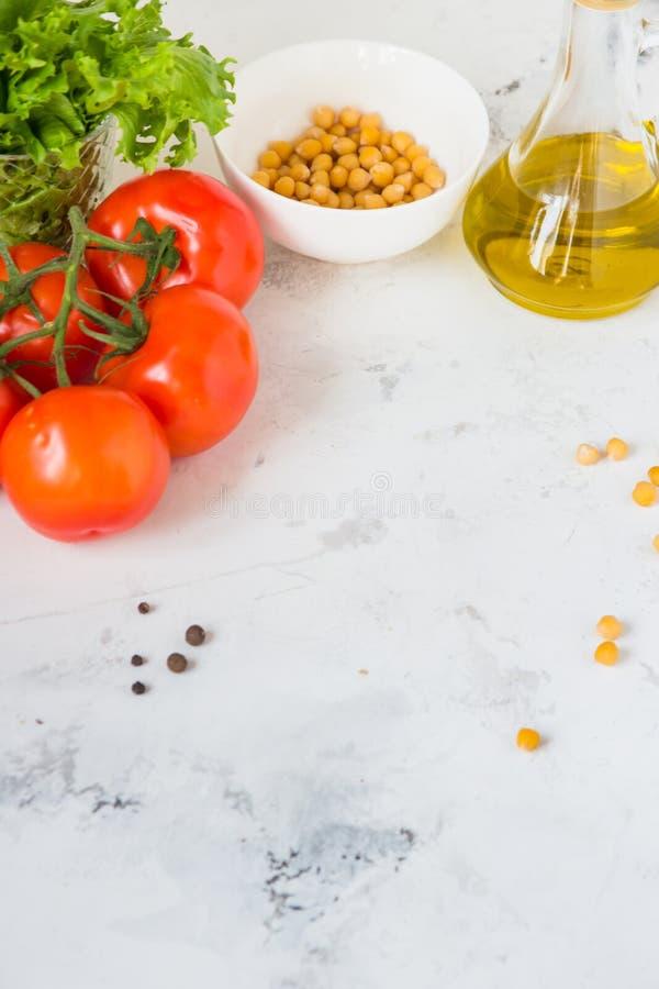 Aceite de oliva, lechuga de la ensalada verde, garbanzo y tomate fresco, copia imagenes de archivo