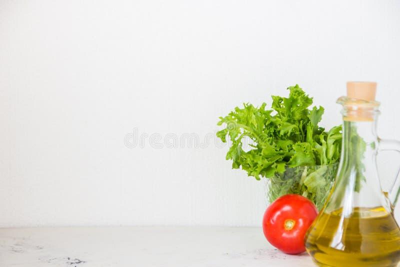 Aceite de oliva, lechuga de la ensalada verde y tomate fresco foto de archivo