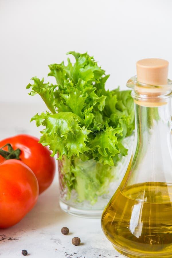 Aceite de oliva, lechuga de la ensalada verde y tomate fresco imagenes de archivo
