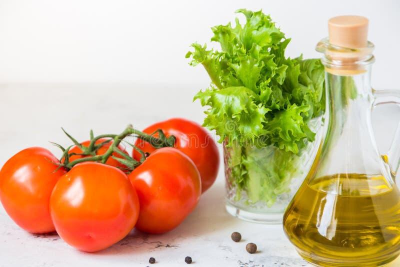 Aceite de oliva, lechuga de la ensalada verde y tomate fresco fotografía de archivo libre de regalías