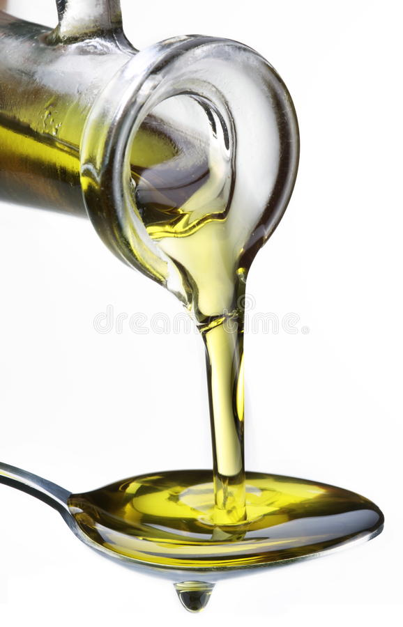 Aceite de oliva que fluye de garrafa en la cuchara. foto de archivo