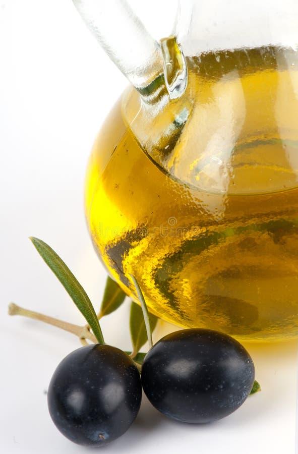 Aceite de oliva virginal adicional con las aceitunas negras. imagen de archivo